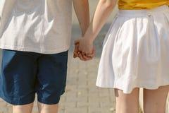 El par joven que camina en el parque y que lleva a cabo las manos, pares cariñosos de A va en una comida campestre Imagen de archivo libre de regalías