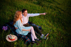 El par joven que se sienta en la tela escocesa en el parque y la mirada en la puesta del sol, el hombre está señalando al horizon Imagen de archivo
