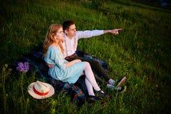 El par joven que se sienta en la tela escocesa en el parque y la mirada en la puesta del sol, el hombre está señalando al horizon Fotografía de archivo