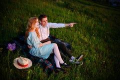 El par joven que se sienta en la tela escocesa en el parque y la mirada en la puesta del sol, el hombre está señalando al horizon Foto de archivo