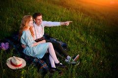 El par joven que se sienta en la tela escocesa en el parque y la mirada en la puesta del sol, el hombre está señalando al horizon Fotografía de archivo libre de regalías
