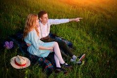 El par joven que se sienta en la tela escocesa en el parque y la mirada en la puesta del sol, el hombre está señalando al horizon Fotos de archivo libres de regalías