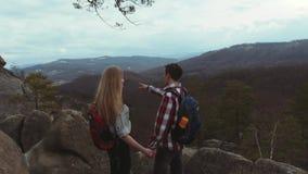 El par joven que sube las colinas rocosas, hombre joven elegante con una mochila da una mano a su novia hermosa con a almacen de metraje de vídeo