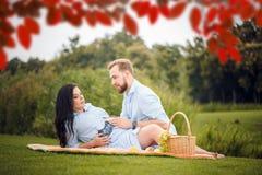 El par joven que tiene una comida campestre en un parque de la ciudad, una mujer está contando con a un bebé imagen de archivo libre de regalías