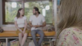 El par joven reconciliado que trabaja en su relación publica durante la sesión de la psicoterapia manejada por el psicólogo del e almacen de metraje de vídeo