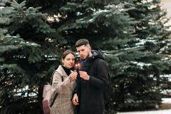 El par joven romántico se está divirtiendo al aire libre en invierno antes de la Navidad con las luces de Bengala imagenes de archivo