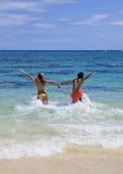 El par joven se ejecuta en el océano Foto de archivo
