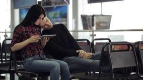 El par joven se está sentando en zona de espera del aeropuerto metrajes