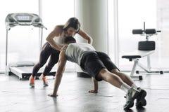 El par joven se est? resolviendo en el gimnasio La mujer atractiva y el hombre muscular hermoso est?n entrenando en gimnasio mode fotos de archivo libres de regalías