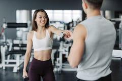 El par joven se est? resolviendo en el gimnasio La mujer atractiva y el instructor muscular hermoso del hombre están entrenando e foto de archivo libre de regalías