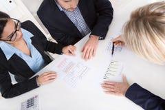 El par joven tiene consulta con el consultor en el escritorio en la oficina. imagen de archivo