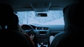 El par joven viaja en coche a través de bosque del invierno almacen de metraje de vídeo