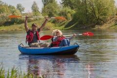 El par kayaking en el río Foto de archivo