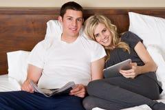 El par lee los ordenadores de la tablilla en cama Fotos de archivo