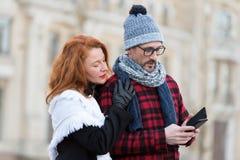 El par lee el mensaje en Smart-teléfono La mujer abraza al hombre con celular El individuo en sombrero y vidrios recibió SMS fotos de archivo