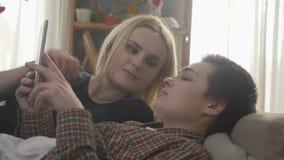 El par lesbiano se está basando sobre el sofá, usando la tableta, enrollando las fotos en la tableta, idilio de la familia, amor, metrajes