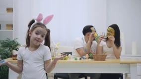 El par lindo colorizing con una ayuda de la brocha de Pascua, en el fondo borroso Su hija dice