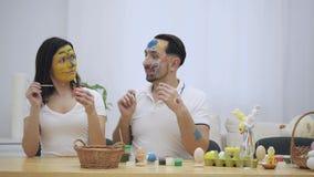 El par lindo colorizing los huevos de Pascua con una ayuda de la brocha, en el fondo blanco borroso Los pares infantiles vinieron