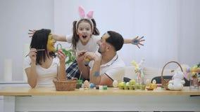 El par lindo colorizing los huevos de Pascua Su hija dice soportes en el sofá, detrás de padres y los asusta infantil