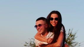 El par lindo europeo joven alegre elegante feliz hermoso en vidrios negros con sonrisas hermosas en uno al ` s arma metrajes