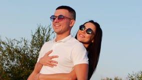 El par lindo europeo joven alegre elegante feliz hermoso en vidrios negros con sonrisas hermosas en uno al ` s arma almacen de metraje de vídeo
