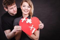 El par lleva a cabo el corazón quebrado unido a en uno imagen de archivo
