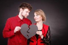 El par lleva a cabo el corazón quebrado unido a en uno imagenes de archivo