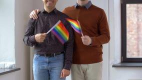 El par masculino con el arco iris del orgullo gay señala por medio de una bandera en casa almacen de video