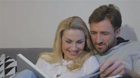 El par mira el álbum de foto en casa