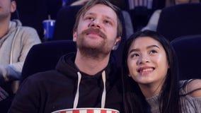 El par mira la película romántica en el cine almacen de video
