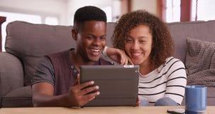 El par negro milenario auténtico se sienta en el piso que mira un vídeo en su tableta fotografía de archivo