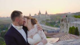 El par precioso de la boda se besa y abrazos cerca de la puesta del sol 4k del castillo metrajes