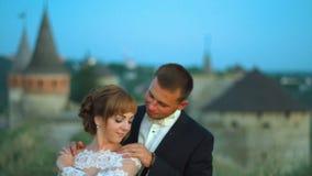 El par precioso de la boda se besa y abrazos cerca de la puesta del sol 4k del castillo almacen de video