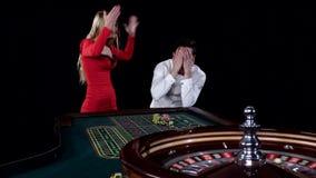 El par que juega la ruleta es impaciente ganar en la casa de juego negro metrajes