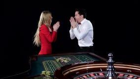 El par que juega la ruleta es impaciente ganar negro almacen de metraje de vídeo