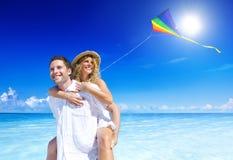 El par que vuela una cometa en la playa Vacations concepto Fotos de archivo