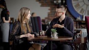 El par recientemente resuelto celebra una reunión en el restaurante para una taza del café, ligones bonitos de una mujer con un h metrajes