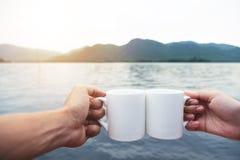 El par relajado da sostener las tazas de café caliente con el río y m Fotografía de archivo