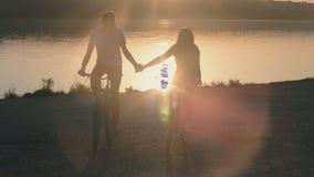 El par romántico en el montar a caballo del amor bikes a lo largo de almacen de video