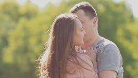 El par romántico en uno al ` s arma en el parque Alegre circundando Besos mutuos almacen de metraje de vídeo