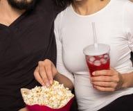 El par romántico está comiendo las palomitas y soda de consumición acogedor cierre Fotos de archivo