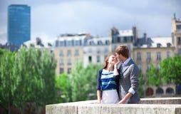 El par romántico se está besando en París en el puente Imagenes de archivo