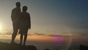 El par se coloca en la roca en la puesta del sol que lleva a cabo las manos almacen de video