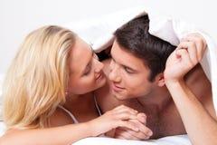 El par se divierte en cama. Risa, alegría y eroticism Foto de archivo