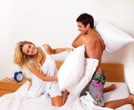 El par se divierte en cama. Risa, alegría y eroticism Imagenes de archivo