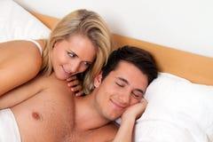 El par se divierte en cama. Risa, alegría y eroticism Fotos de archivo libres de regalías