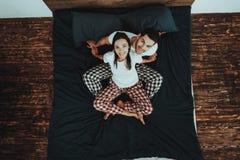 El par se está sentando en cama y está mirando para arriba foto de archivo