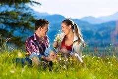 El par se está sentando en el prado con la montaña Foto de archivo