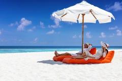 El par se relaja en una playa tropical durante sus vacaciones de verano foto de archivo libre de regalías