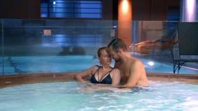 El par se relaja en una tina caliente al aire libre Mujer joven feliz y hombre que se relajan en agua caliente cerca de la piscin almacen de metraje de vídeo